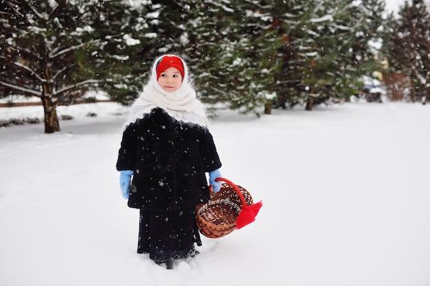 子の女の子の毛皮のコートと手で枝編み細工品バスケットを持ってロシア風のスカーフ