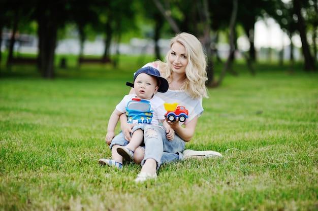 緑の芝生の背景にキャップのママとベビーの息子