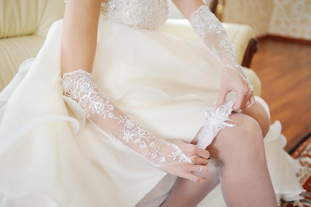 花嫁は結婚式のガーターを脚にかけます