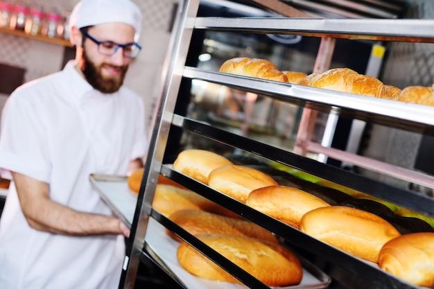 Пекарь в форме, держа поднос, полный свежеиспеченного хлеба в процессе производства, на задней части пекарни