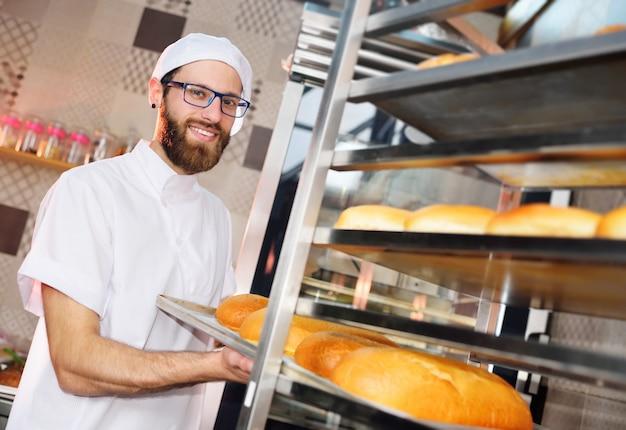 Молодой привлекательный пекарь ставит поднос со свежей выпечкой на полку на поверхность пекарни или хлебозавода.