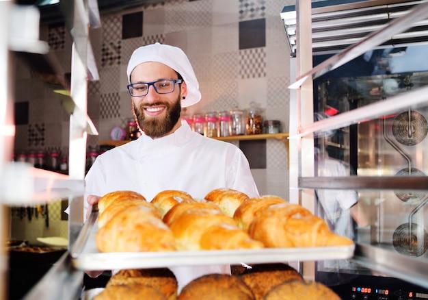 Красивый пекарь в белой форме держит в руках поднос, полный свежеиспеченных круассанов на поверхности пекарни