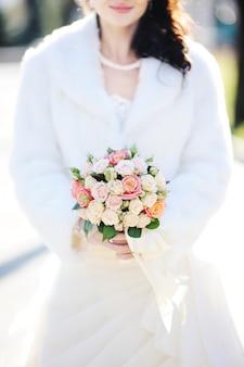バラの美しいウェディングブーケを持つ花嫁。