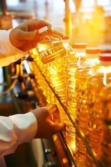 ひまわり油。ヒマワリの種から精製された油の生産と瓶詰めのライン。食品産業のコンベヤー