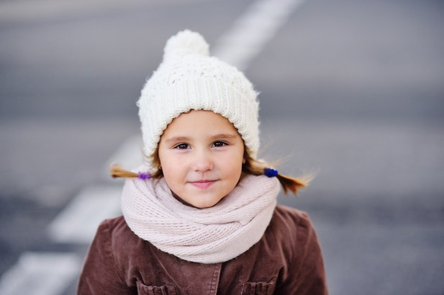 白い暖かい帽子とスカーフの少女の子供の肖像画。暖かい服。秋、冬。子供のファッション
