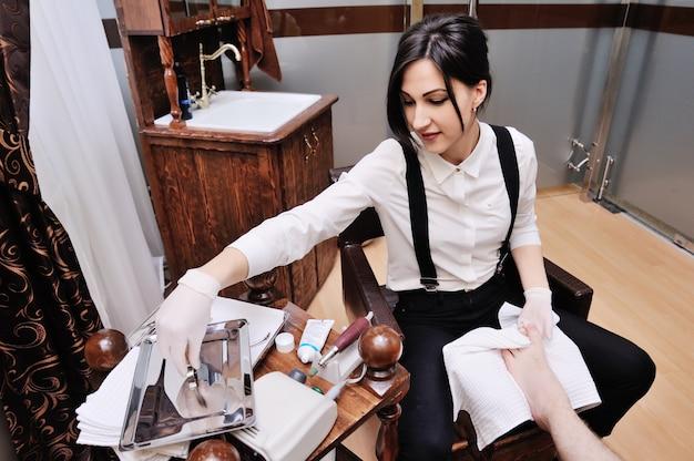 Молодая девушка делает мужскому педикюру на поверхности салона красоты. уход за ногтями