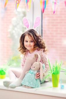 彼女の手でイースターのウサギとピンクのウサギの耳を持つ子供の女の子