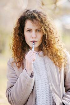 女性が電子タバコを吸う