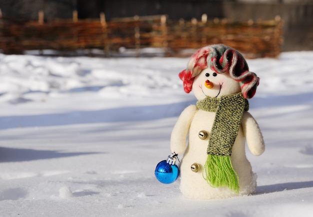 雪の中で立っている手の中のクリスマスのおもちゃのおもちゃ雪だるま