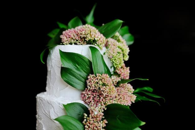 ライラック色の花と黒の背景に緑の葉で飾られた豪華なウェディングケーキ
