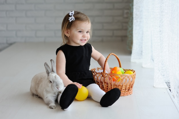 Маленькая девочка с пасхальной корзинкой и пасхальным кроликом