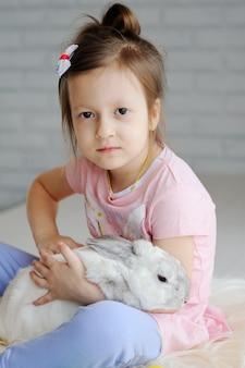 Маленькая девочка с кроликом на белом фоне