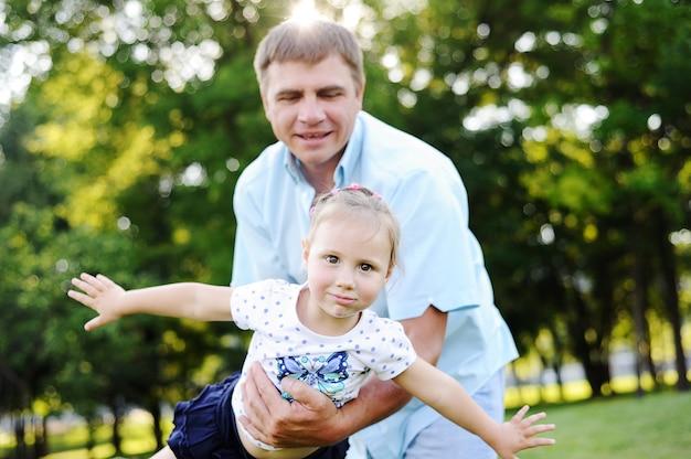 木の背景に公園で彼の娘と遊ぶの父