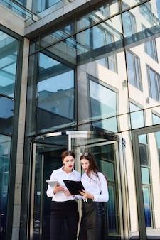 Две девушки в деловой одежде на фоне офисного здания