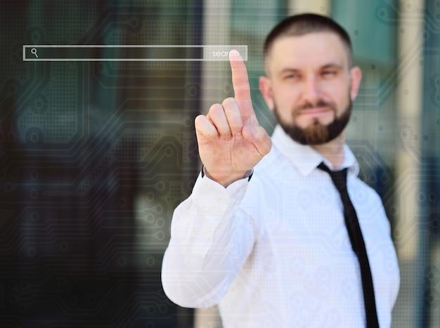 仮想タッチスクリーンで彼の指を指している若い男