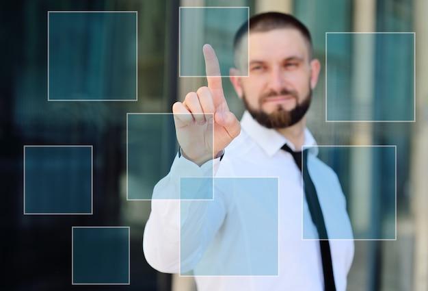 白いシャツとネクタイの若い男がタッチスクリーンの仮想画面に彼の人差し指を押しています。