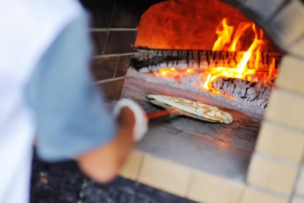 Ручной повар или пекарь с аппетитной пиццей