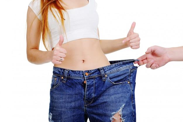 Девушка в большом размере брюк на белой предпосылке. рука рисует красивую девушку. потеря веса
