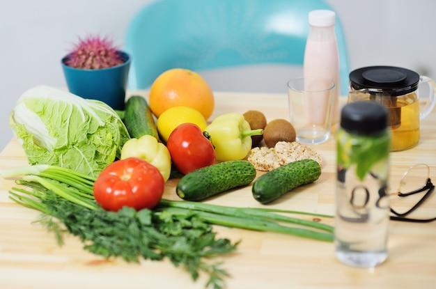 木製のテーブルトマト、キャベツ、コショウ、きゅうり、ハーブ、ケフィアの野菜のクローズアップ。