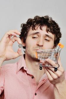 小さなスーパーマーケットのトロリーと白い背景の上の鉄のコインを持つ男。