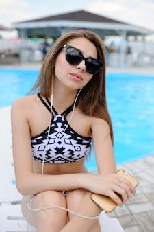 Девушка в черном купальнике сидит на фоне бассейна и слушает музыку в белых наушниках.