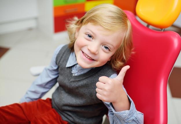 歯科用椅子に金髪の巻き毛を持つ男の子の笑顔。