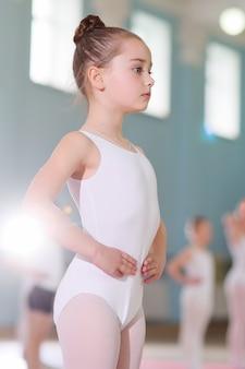 バレエスタジオの若いダンサー。若いダンサーは、教室でのウォームアップ中に体操を行います。スポーツ、体操、子どもの発達