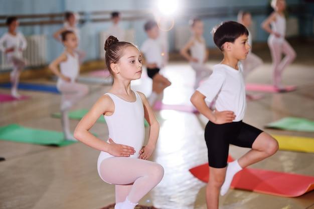 Группа детей в балетной школе или в секции гимнастики на каримат