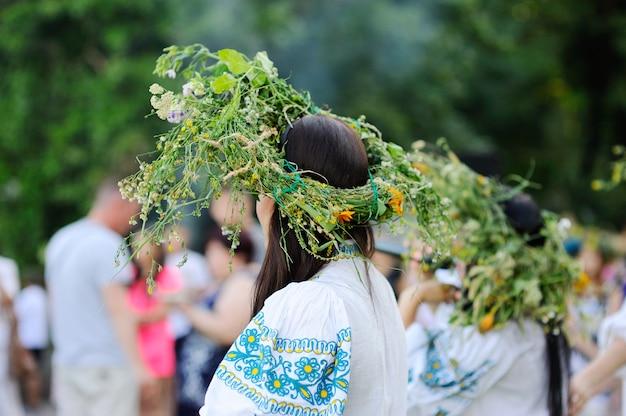 野生の花の花輪を持つ女の子はラウンドダンスを運転