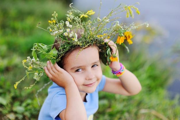 野生の花の花輪の女の赤ちゃん