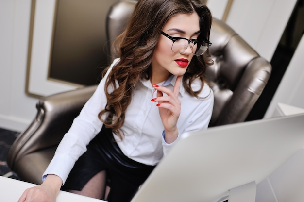 白いシャツを着たかわいい女の子は、コンピューターのモニターに座っています。