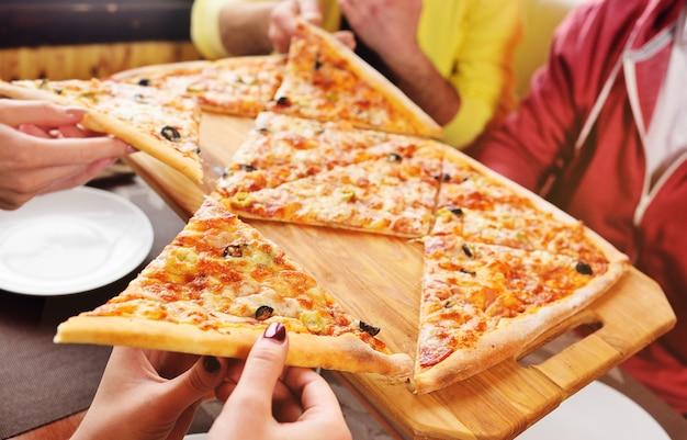 友人のグループがカフェに座って新鮮な熱いピザをつかみます。ピザのクローズアップのスライスと手。