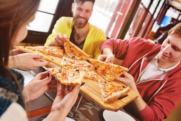 友達のグループが話し、カフェで笑ってピザを食べます。