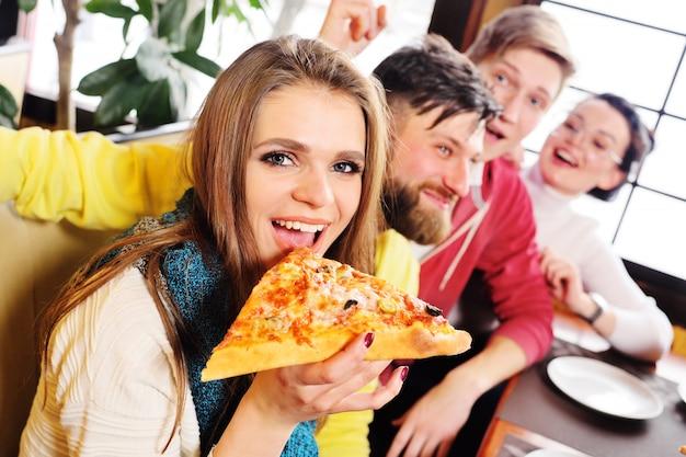 友達のグループがカフェで新鮮なおいしいピザを食べて、話して笑っています。