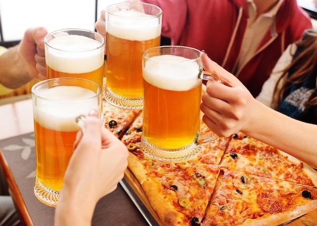 ピザの背景にビールのクローズアップのグラスを持つ手。