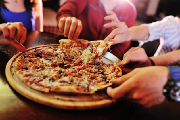 人々の友人のグループや会社の背景にあるテーブルの上のホットピザのクローズアップ