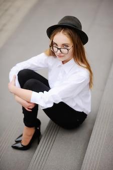 Девушка в очках и винтажной шляпе сидит на ступеньках