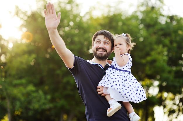 彼女の腕の中で小さな娘を持つお父さん。お父さんと娘のさようなら