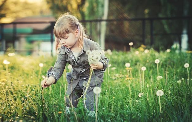 赤ちゃんの女の子が花を摘む緑の牧草地の背景にある女の子。