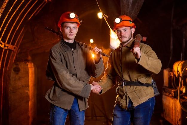 Два молодых парня в рабочей форме и защитных шлемах, пожимающие друг другу руки. рабочие шахты. шахтеры