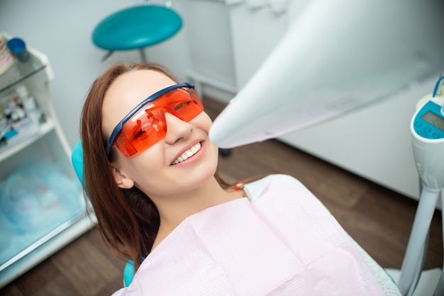 歯科医の椅子に美しい、陽気な女の子