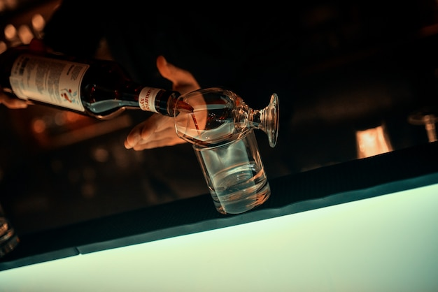 バーテンダーの手、バーカウンターの上にガラスのゴブレット