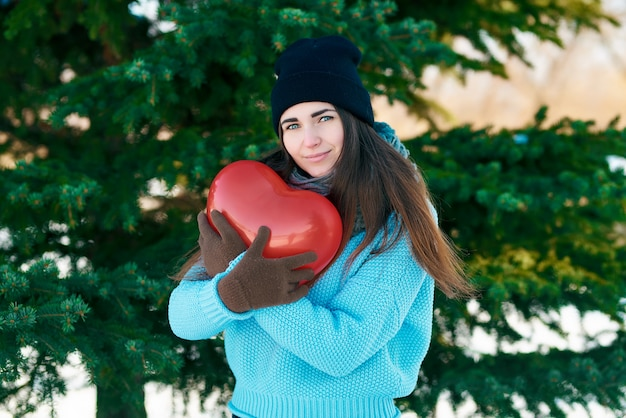 手でハートの形をした風船を持つ少女。バレンタイン・デー