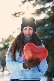 バレンタインの日の手でハート形の風船で美しい少女