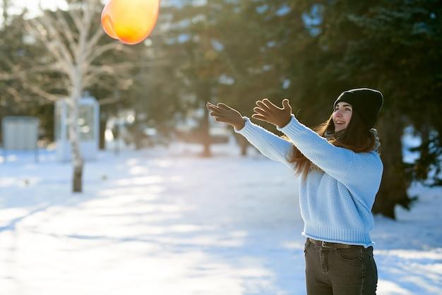 美しい少女は、バレンタインの日にハートの形をした風船をキャッチします。