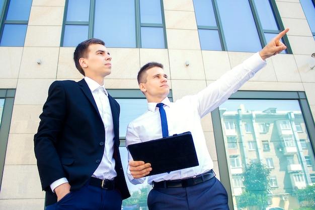 Двое мужчин ведут диалог возле бизнес-центра