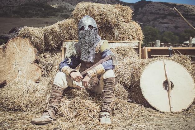 バイキングの衣装を着た男が干し草の上に座っている