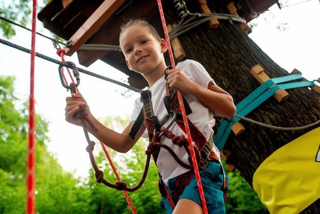 Маленький мальчик проходит полосу препятствий в веревочном парке