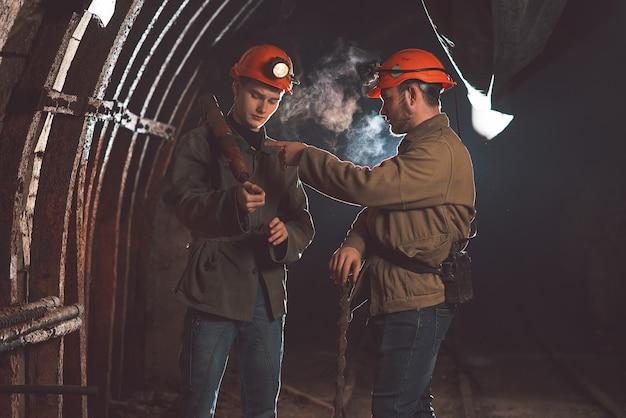 Двое молодых парней в специальной одежде и шлемах стоят в шахте