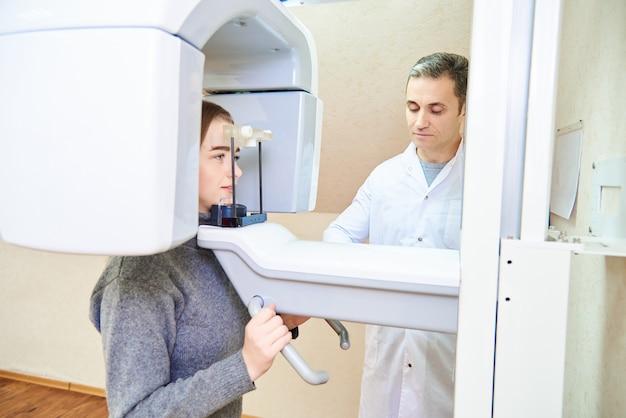 歯科断層撮影。断層撮影、コントロールパネルの近くの医者に立っている少女患者